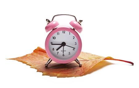 Pink alarm clock on white background.