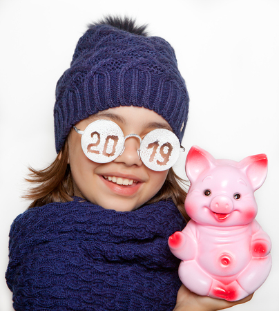 Cheerful girl with glasses with piggy bank