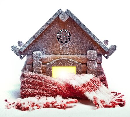 Christmas snow-covered wooden house wrapped in a warm knitted scarf
