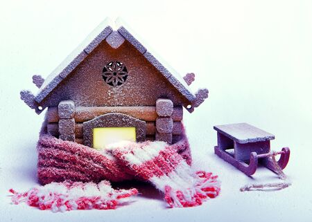 Christmas snow-covered wooden house, wrapped in a warm knitted scarf and sled. Imagens