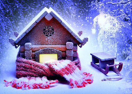 Christmas snow-covered wooden house in the woods, wrapped in a warm knitted scarf and sled. Collage