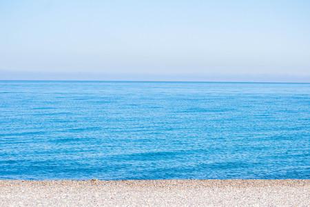 Blue sea, sea coast, small stones. Summer sunny day. Natural concept.