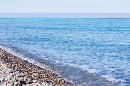 Blue sea, sea coast, small stones. Natural concept. Summer sunny day.