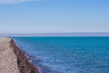 Waves in the sea. Blue sea, sea coast, small stones. Summer sunny day. Natural concept. Banco de Imagens