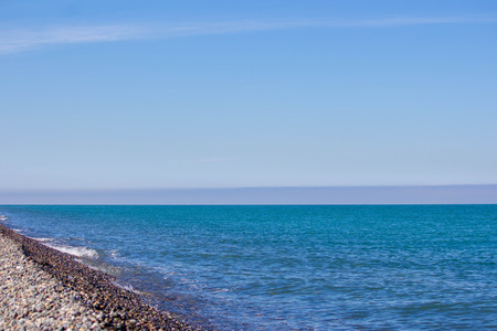 Natural concept. Blue sea, sea coast, small stones. Summer sunny day. Banco de Imagens