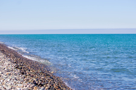 Natural concept. Blue sea, sea coast, small stones. Summer sunny day. Waves in the sea.