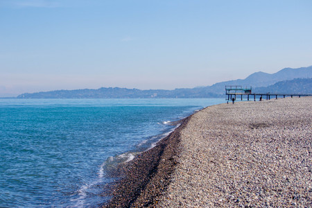 Blue sea, sea coast, small stones. Mountains in the distance. Waves in the sea. Summer sunny day. Natural concept. Banco de Imagens
