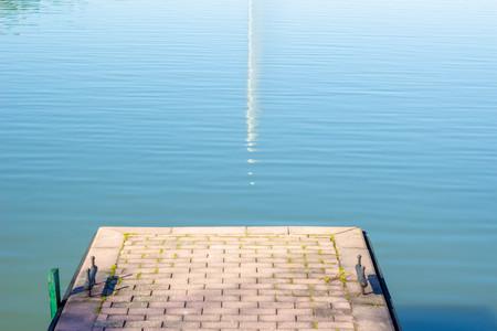 A small pier near the water. Lake with a pier. Sea, ocean. Natural concept. Banco de Imagens