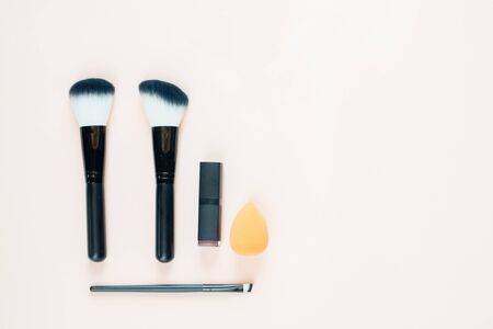 Makeup brushes and lipstick. Place for text. Flat layout.