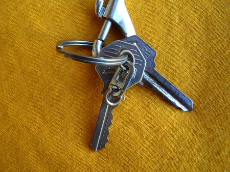 Two keys on a metal keholder over yellow background Stock fotó