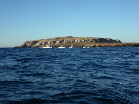 blue waters: View of an island surrounded by dark blue waters