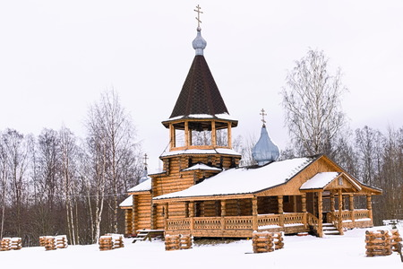 Wooden church with belfry, among the trees in winter in Russia 免版税图像