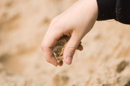 The hand of a boy dressed in a hoodie pours sand on the beach.