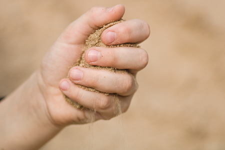The hand of a child squeezes a handful of sand