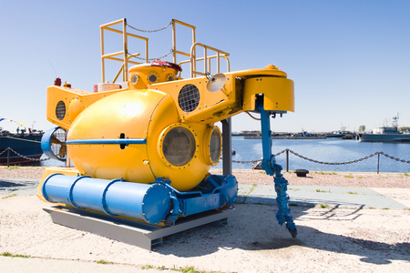 Small yellow rescue bathyscaphe with illuminators and mechanical manipulators