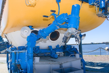 Big yellow and blue bathyscaphe with illuminators and mechanical manipulators close up