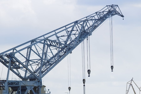 The arrow of a huge port crane with a lot of cables and hooks against the cloudy sky