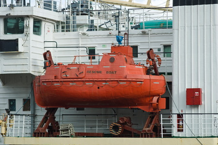 A large red spastelnaya boat with a sealed cabin portholes installed in the device for launching it into the water.