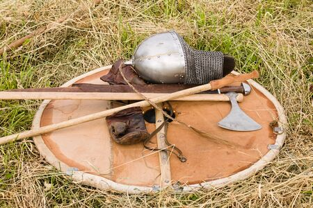 Helmet spear and ax folded on a shield lying on the grass on the ground. The weapon is folded after the fight at the festival.
