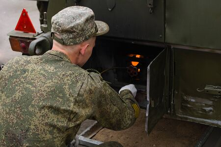 A soldier lights a fire in the field kitchen for cooking