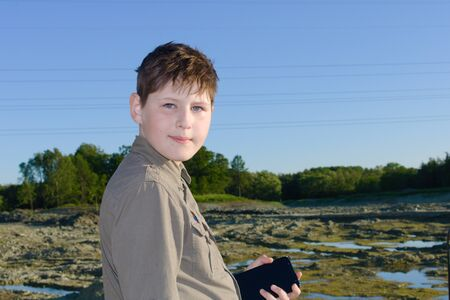 A boy with tousled hair in a green shirt holds a mobile phone in his hand against the background of a drained riverbed in the summer. Ecological vacation.