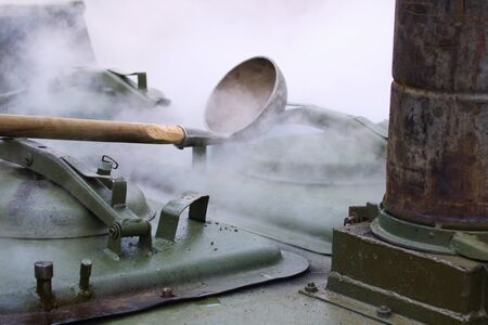 The ladle lies on a green metal marching army boiler in which porridge is cooked. Steam comes from the boiler.