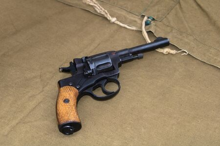 WWII black revolver with wooden handle rests on green canvas