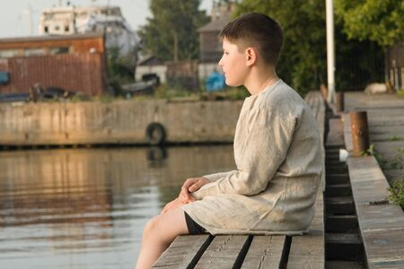 A boy in a linen shirt sits on the edge of a wooden pier in the summer and looks at the water
