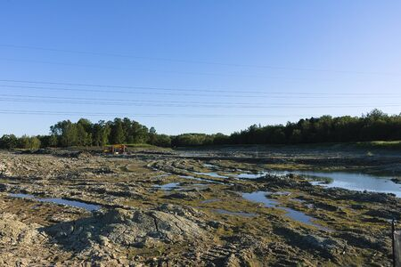 Drained riverbed against the backdrop of the summer forest. Construction of hydraulic structures. Caring for the environment.