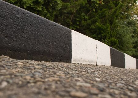 A street border painted in white and black on the background of the road and green foliage in the summer closeup. Road safety