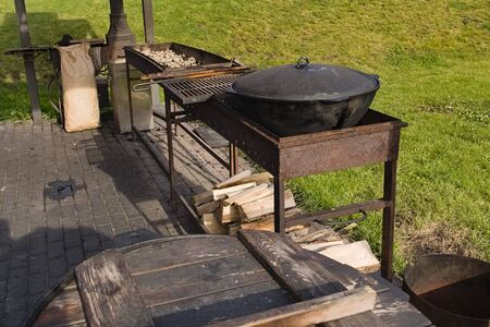 Wooden platform for cooking outdoors with a rusty barbecue, a cauldron for cooking pilaf with a wooden barrel and firewood Banco de Imagens