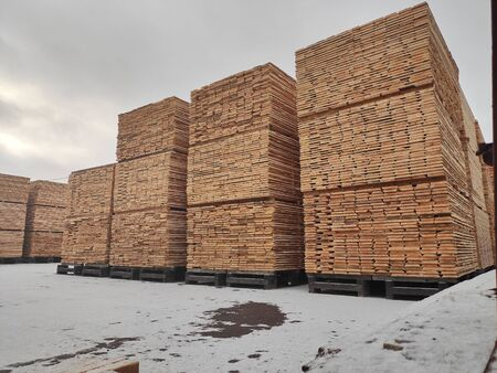 Natural wood boards stacked in a stack at an open lumber warehouse in the snow Zdjęcie Seryjne