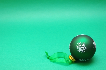 Green Christmas bauble with green background and space