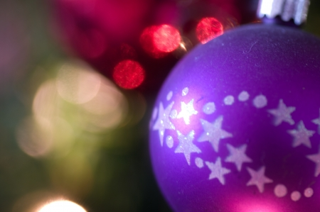 Purple bauble decorated with stars with bokeh to left Stock Photo - 21924856