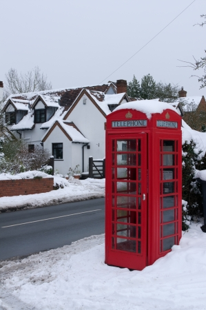 Red British telephone kiosk in snow