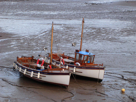 Two boats moored on mud of harbour when tide out  Editorial
