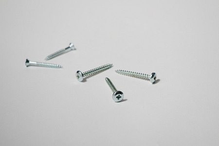 uncluttered: Five screws on uncluttered background Stock Photo