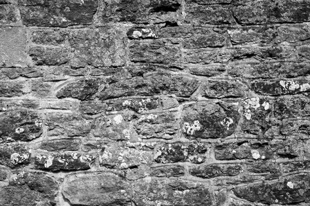 Weathered Cotswold stone wall with lichen
