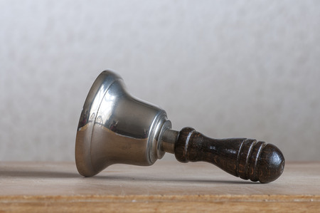 handbell: Hand bell lying on wooden board Stock Photo