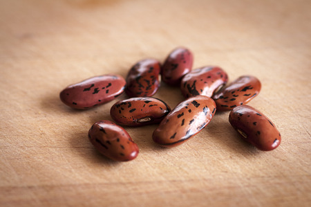 Wisley Magic runner beans dried ready for sowing, on wooden board