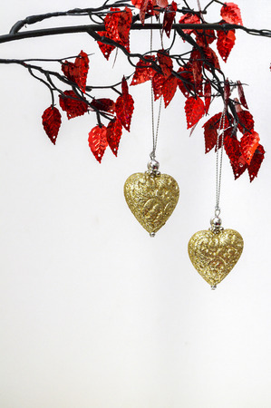 Two golden Christmas hearts decorations hanging from red leaves.