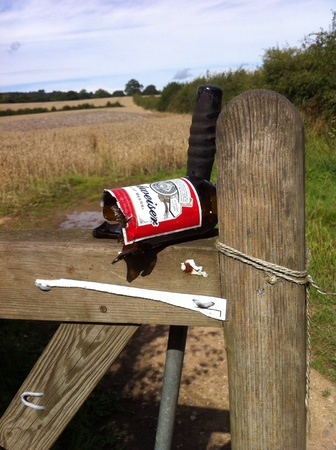 Broken beer bottle lodged dangerously on a country gate leading to a popular rural path Stock Photo