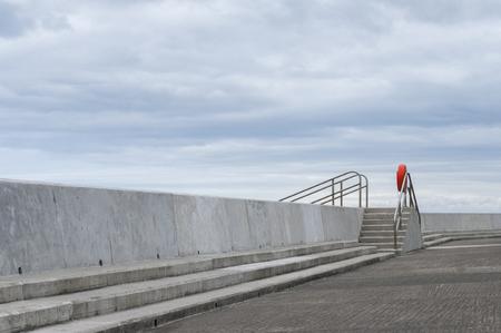 Coastal sea defences with steps and lifebuoy.