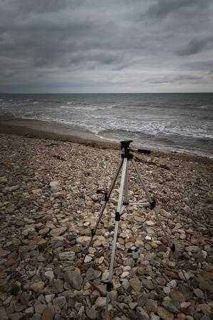 shingle beach: Tripod on shingle beach in bad weather Stock Photo