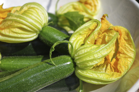 courgettes: Fresh courgettes with flowers on in white bowl. Stock Photo