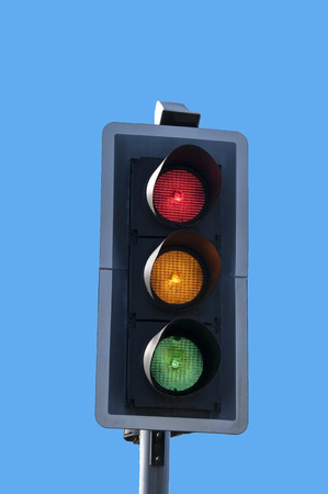 Red, amber and green traffic lights all on together against blue sky background. Stock Photo