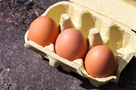 Three large eggs in yellow box on paving. Diagonal. In sunlight. Stock Photo