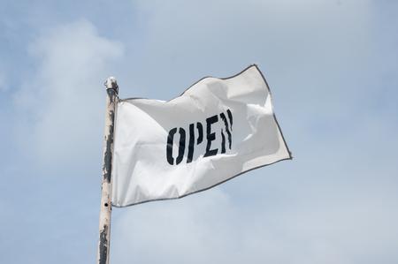 letras negras: La palabra abierta en letras negras sobre una bandera blanca.