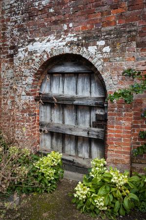 Old weathered wooden garden door in brick wall. Stock Photo