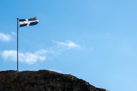 Cornish flag flying on the rocks at Perranporth.